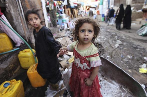 Children fill containers with drinking water in the Old City of Sanaa