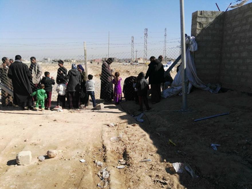 سكان مخيم الشهامة يتكلمون مع أقاربهم من خلال سياج المخيم.